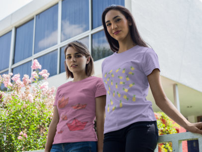 Pair of Beautiful Girls Wearing Round Neck Tees Template While Near a White Building Outdoors a16252