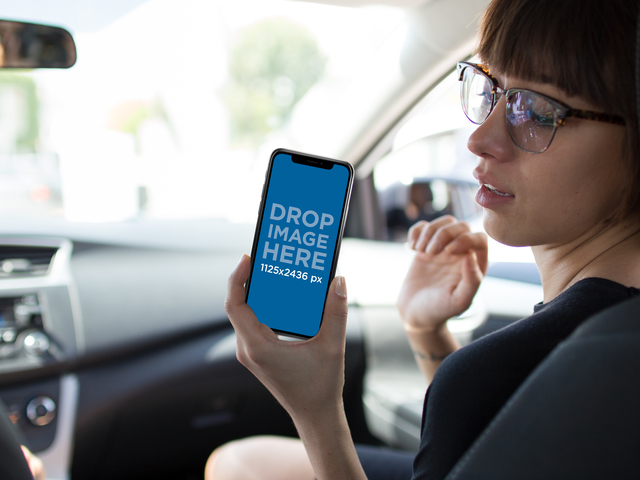 Hipster Woman Showing her iPhone X Mockup While in the Passenger Seat a17375