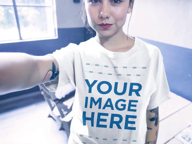 Girl Taking a Selfie Video While Wearing a T-Shirt Mockup Indoors a17119