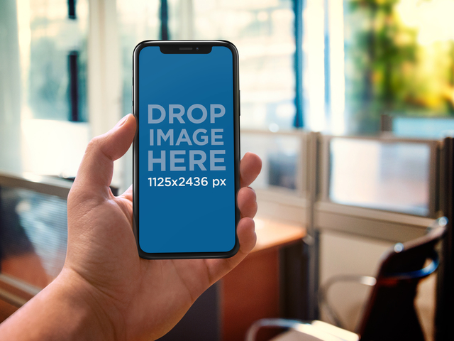 Placeit Iphone X Mockup Being Held Against An Office