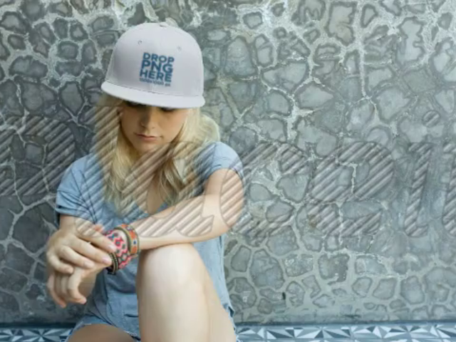 Blonde Girl Wearing a Snapback While Sitting Down Against a Wall Video Mockup a14141