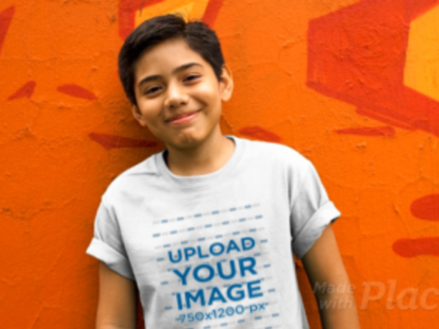 Boy Wearing a Kid's Round Neck Tee Video Standing Against a Painted Wall 12769