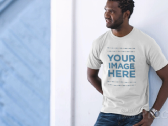 Young Black Man Laughing Wearing a T-Shirt Video and Leaning Against a Wall a12776