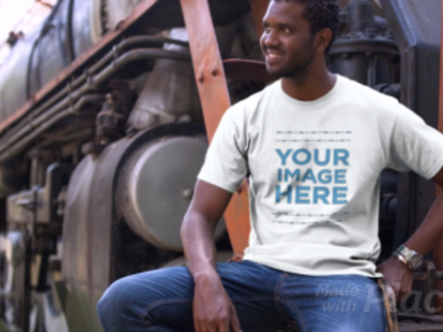 Smiling Black Man Sitting Next to a Train Wearing a T-Shirt Video Mockup a12779