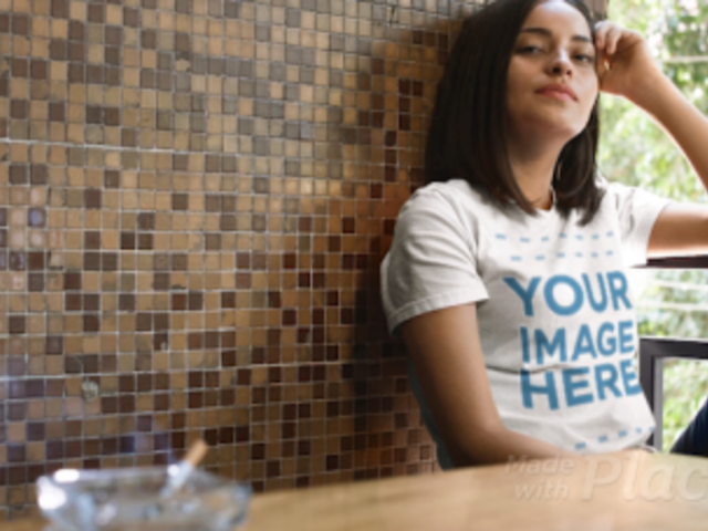 Girl Wearing a T-Shirt Sitting Near a Cigarette in Ashtray Apparel Video Mockup a13401