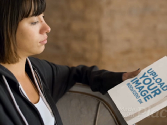 Short Haired Girl Holding a Book Video Mockup while Sitting a14064