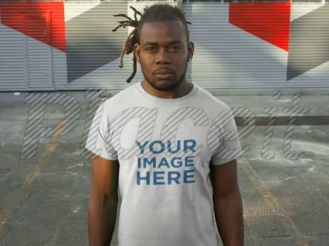 Young Man With Dreadlocks Standing in a Parking Lot Wearing a T-Shirt Video Mockup a12237