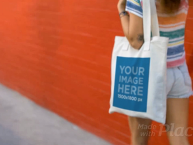 Young Pretty Girl Carrying Tote Bag Video Against a Red Wall a13715