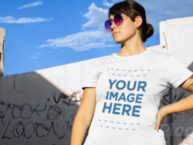 Woman Wearing a Round Neck Tee Video Mockup in a Sunny Day Near Graffiti Walls a12644