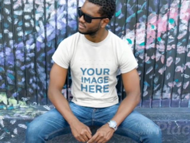 Young Black Man Wearing a T-Shirt Video and Sunglasses while Sitting Near a Painted Wall a12116