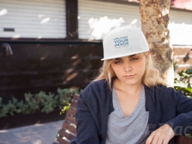 Blonde Girl Wearing a Snapback Hat Video Mockup While Sitting on a Bench Outdoors a14142