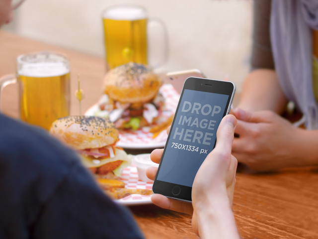 iPhone 6 Mockup At A Hamburger And Beer Place With Friends Placeit Stage Image