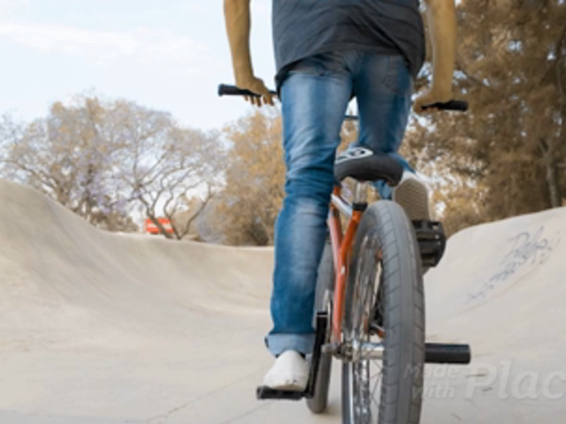 Dude Riding a BMX Bike While Wearing a Snapback Hat Backward in a Skatepark Video Mockup a14191