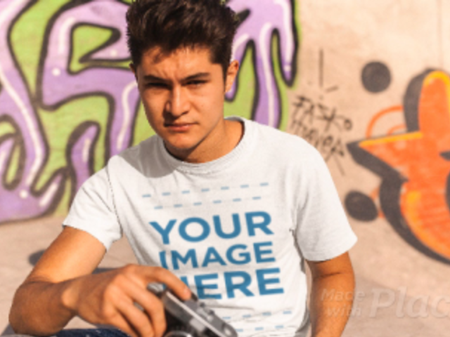 Young Man with a Vintage Camera Wearing a T-Shirt Stop Motion at a Skating Park a13503