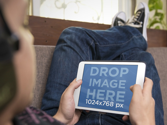 iPad Mockup Template Featuring a Teenager Using White iPad on the Couch Placeit Stage Image