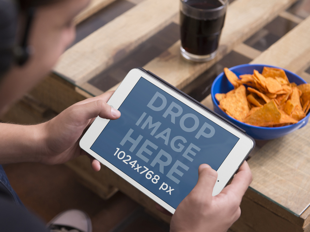 Tablet Mockup of Teenager Using iPad Mini With a Bowl of Chips and Soda Placeit Stage Image