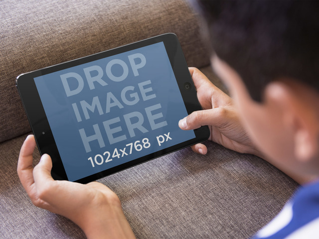 Tablet Mockup of Boy Playing With iPad Mini on the Couch Placeit Stage Image