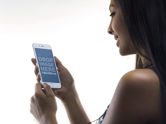 Pretty Young Woman Using her iPhone on a Plain White Backdrop