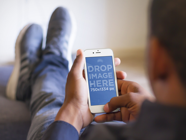 Mockup of Man Relaxing With His Feet Up While Using a White iPhone 6 Placeit Stage Image