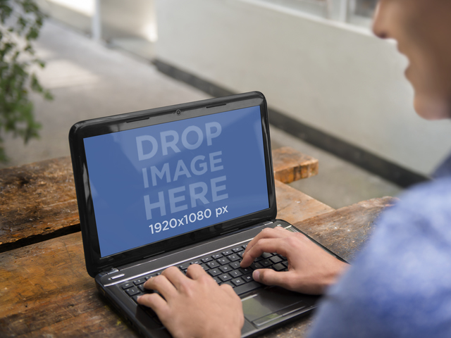 Young Man Using his HP Laptop on an Outdoor Table Placeit Stage Image