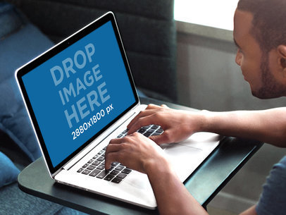 Young Man Working on a Macbook Pro at a Creative Office