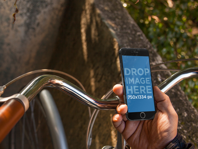 iPhone 6 Mockup Featuring a Man Riding a Vintage Bicycle