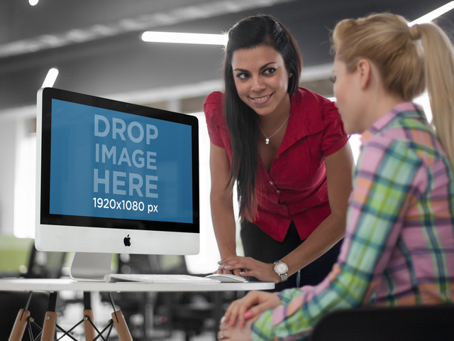 Two Young Businesswoman Chatting in Front of an iMac Mockup a5187