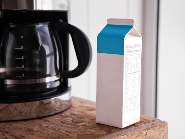 Label Mockup of a Milk Carton Standing Next to a Coffee Machine a6696