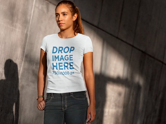 T-Shirt Mockup of a Woman Standing Next to a Concrete Wall 6569a