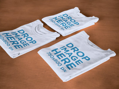 Folded T-Shirts Mockup Lying on Top of a Wooden Surface6482a