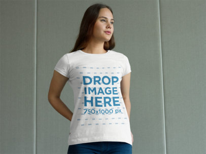 T-Shirt Mockup of a Woman Standing in Front of a Wall a7987