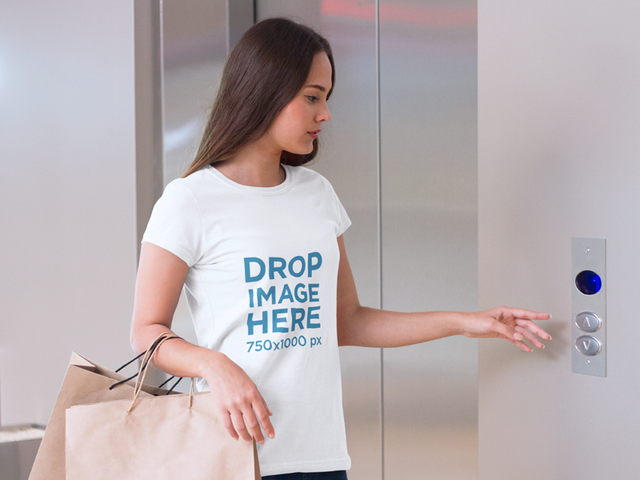 T-Shirt Mockup Featuring a Woman Waiting for an Elevator a7988