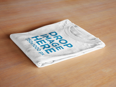 Folded T-Shirt Mockup Lying Over a Table Surface a6480