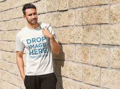 Young Man Standing Next to a Brick Wall T-Shirt Mockup a8018