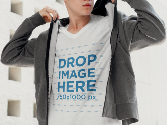 Young Man on the Street Fixing his Hoodie T-Shirt Mockup a5560