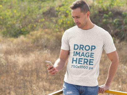 Man Using an iPhone Outdoors T-Shirt Mockup a8674