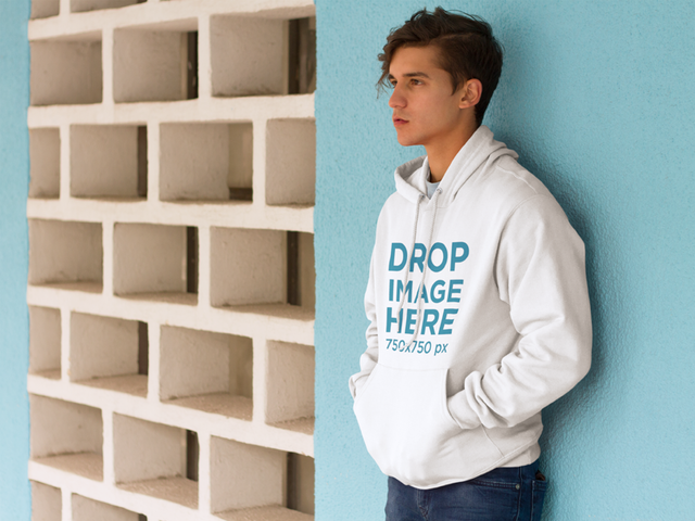Young Man Leaning Against a Blue Wall Hoodie Mockup a8644