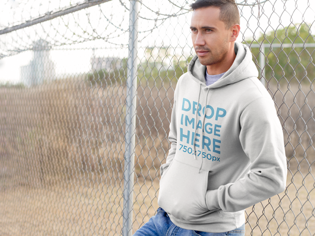 Man Leaning on a Wire Fence Hoodie Mockup a8688