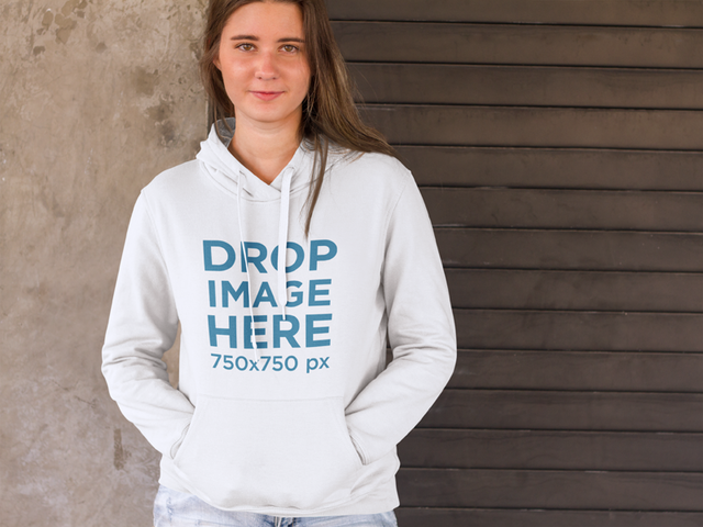 Girl Standing in Front of a Concrete Wall Hoodie Mockup a9006