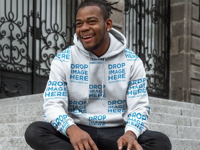 Hoodie Mockup of a Smiling Black man Sitting outside an Old Building aa9296