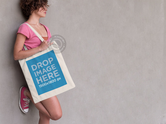 Woman Leaning Against a Wall With a Tote Bag Mockup a11450