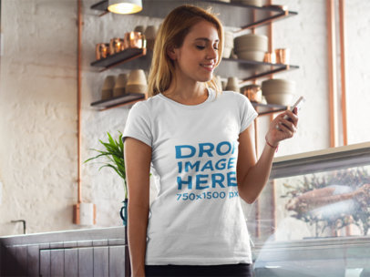 T-Shirt Mockup of a Young Woman Texting at Home 8139