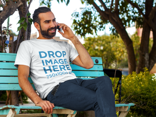 T-Shirt Mockup of a Smiling Man Sitting on a Bench a8231