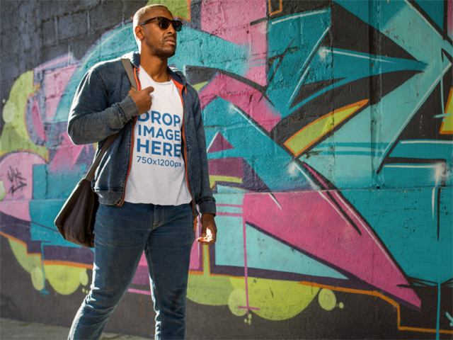 Tee Mockup of a Black Man Walking by a Graffiti Wall a8976