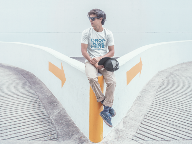 T-Shirt Mockup of a Trendy Guy Sitting in a Parking Lot a11588a