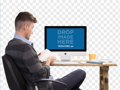iMac PNG Mockup of a Man Reading at His Desk a11725