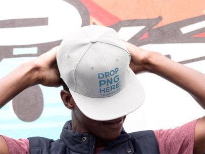 Snapback Hat Mockup of a Young Black Man Near a Graffiti Wall 11768