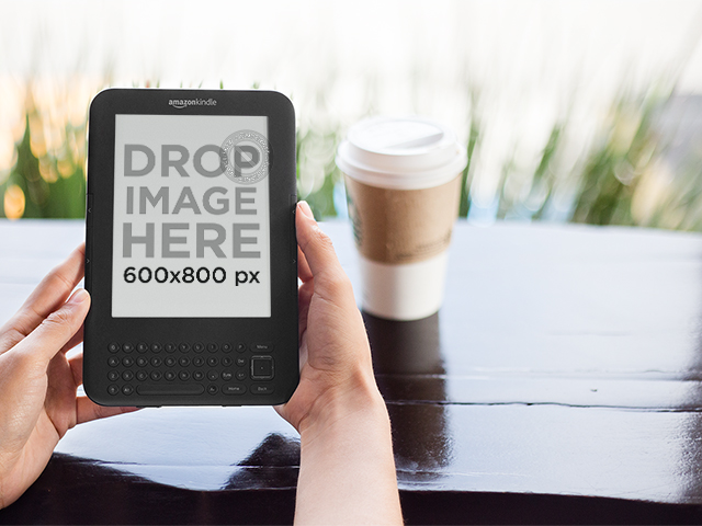Kindle Held with Both Hands at a Coffee Shop Mockup a11835print