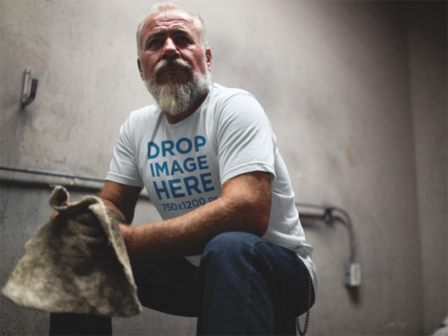 T-Shirt Mockup of a Senior Man Crouching in a Garage a12061