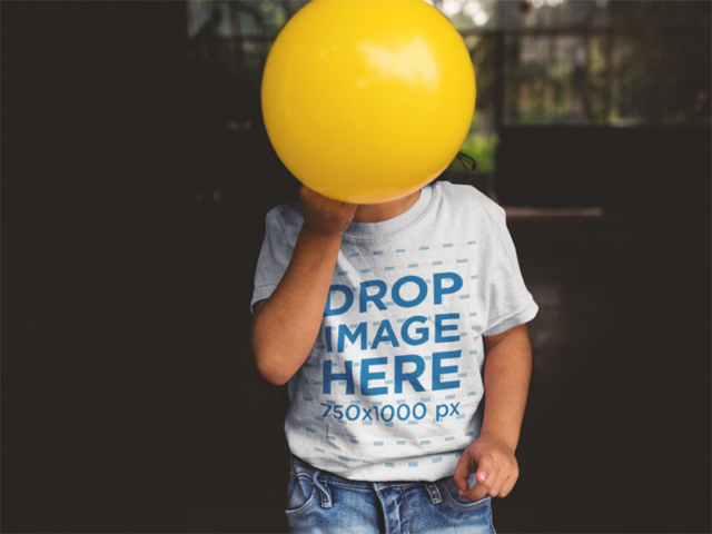 Kid's T-Shirt Mockup of a Child Covering Their Face with a Ball a12103